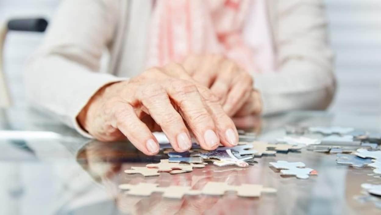 Gros plan sur la main d'une personne agée qui joue à un puzzle.