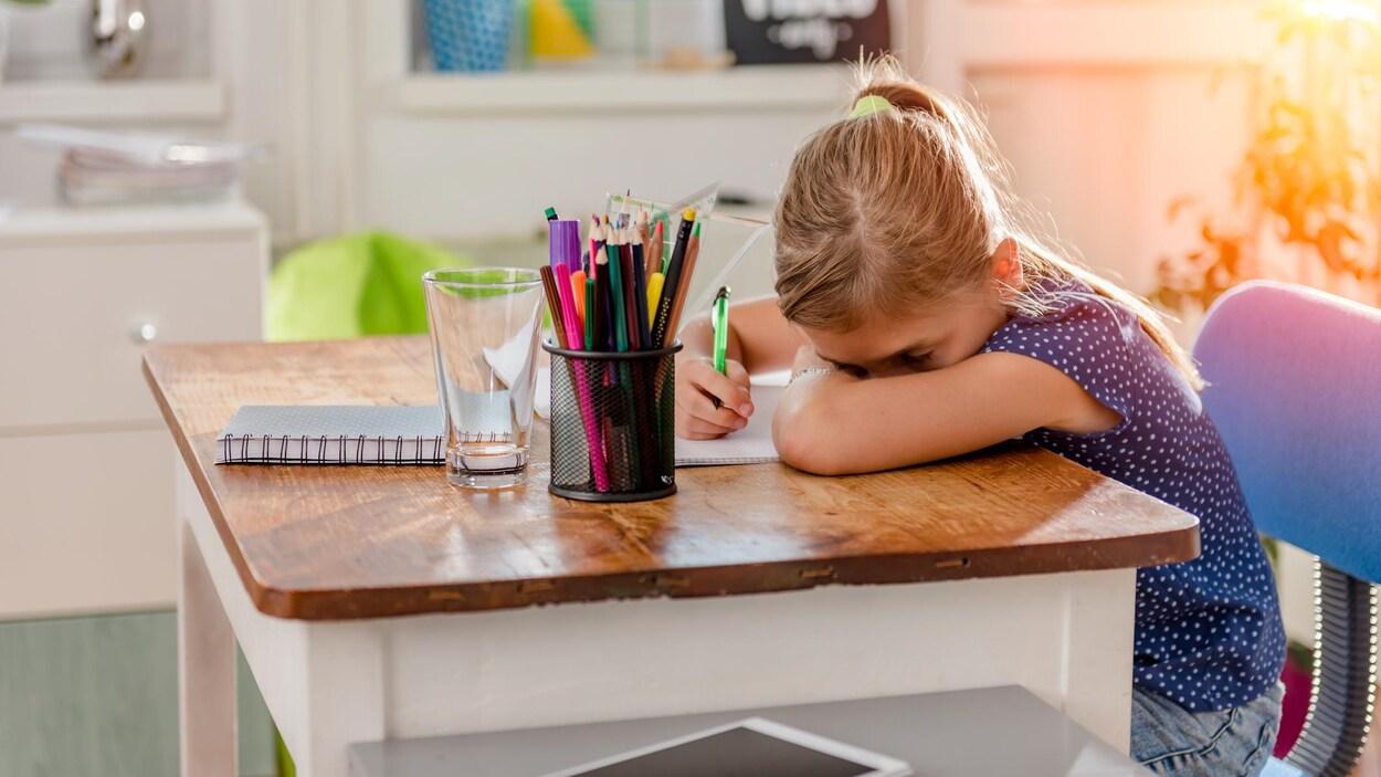 Une jeune élève semble avoir du mal à se concentrer en faisant ses devoirs.