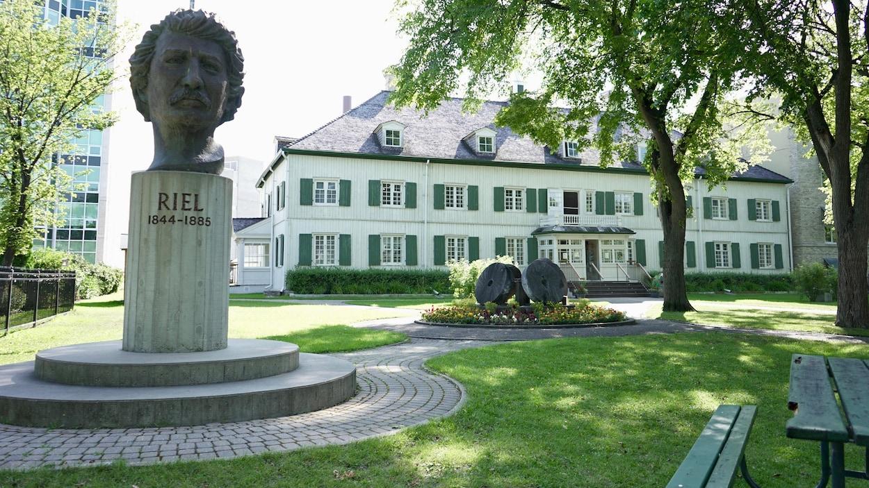 La tête en bronze de Riel trône devant un édifice historique.