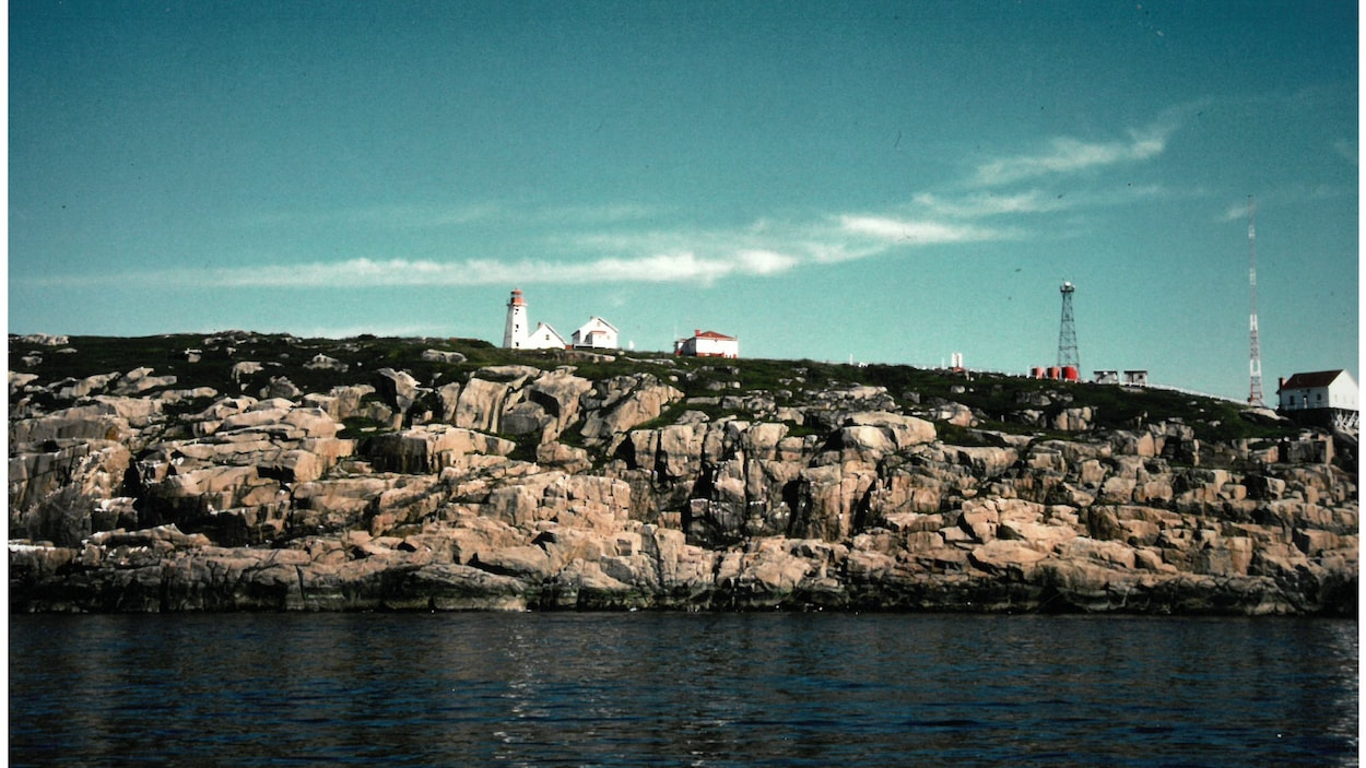 Le phare, d'autres bâtiments tout près et des antennes sur l'île rocheuse en 1985.