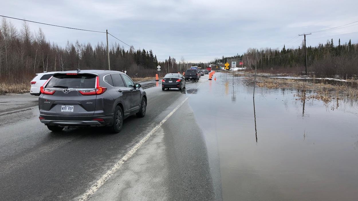 Une route est recouverte d'eau et des automobilistes circulent au ralenti.