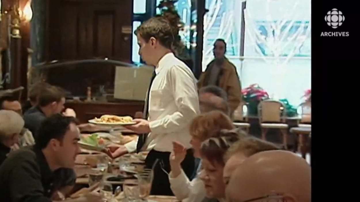 Un serveur apporte à une table des assiettes aux clients dans un restaurant.