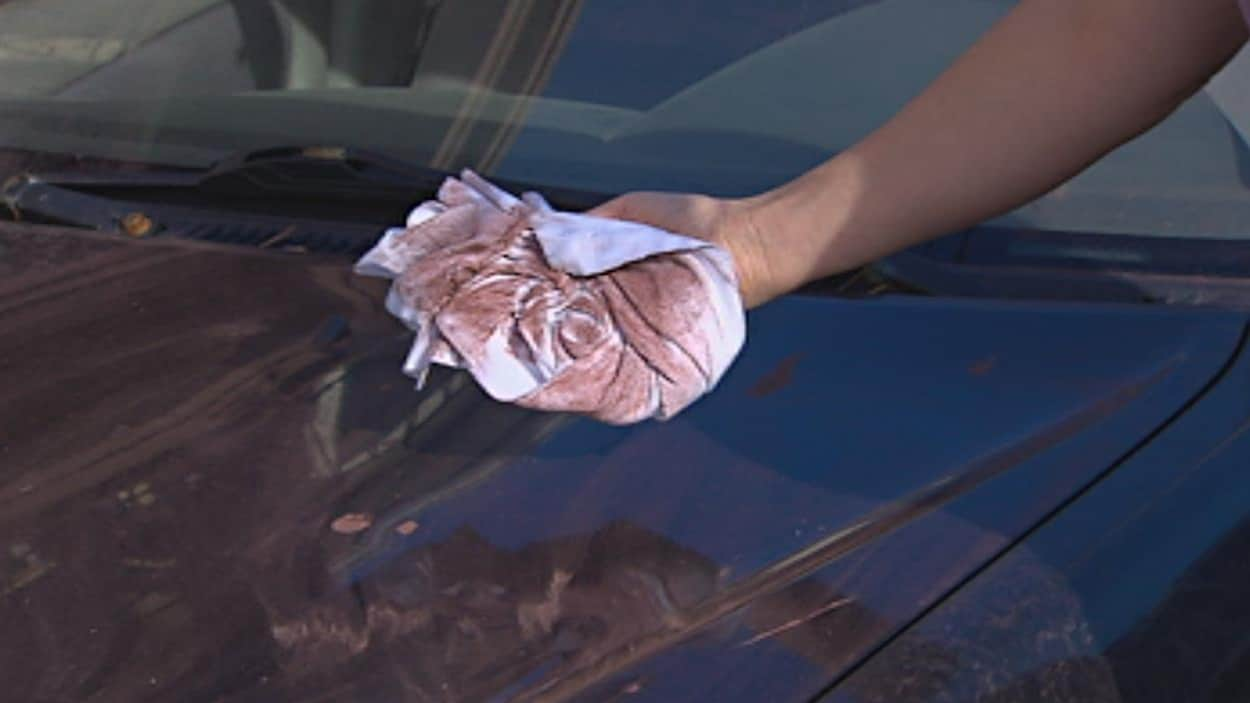 Une main brandit un chiffon blanc maculé de poussière rouge après avoir été utilisé pour essuyer le capot d'une voiture.