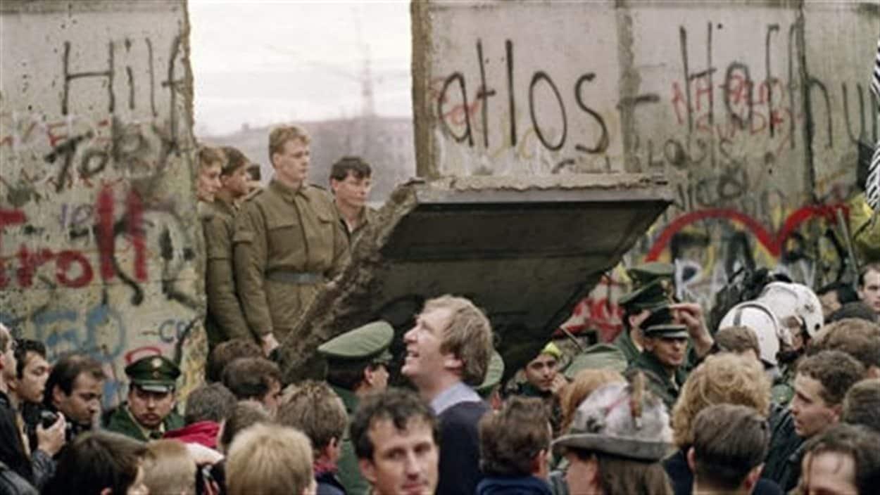 Des soldats sont debout sur un des panneaux tombés du mur de Berlin et regardent la foule massée tout près.