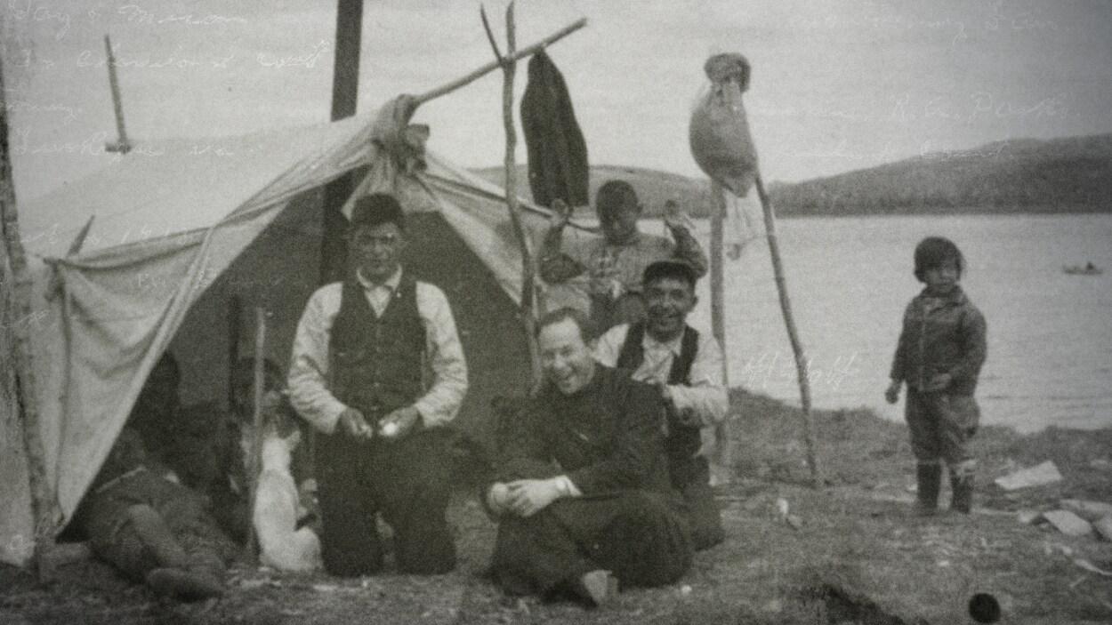 Le père Alexis Joveneau avec une famille innue. Ils sont tous assis près d'une tente, au bord de l'eau.