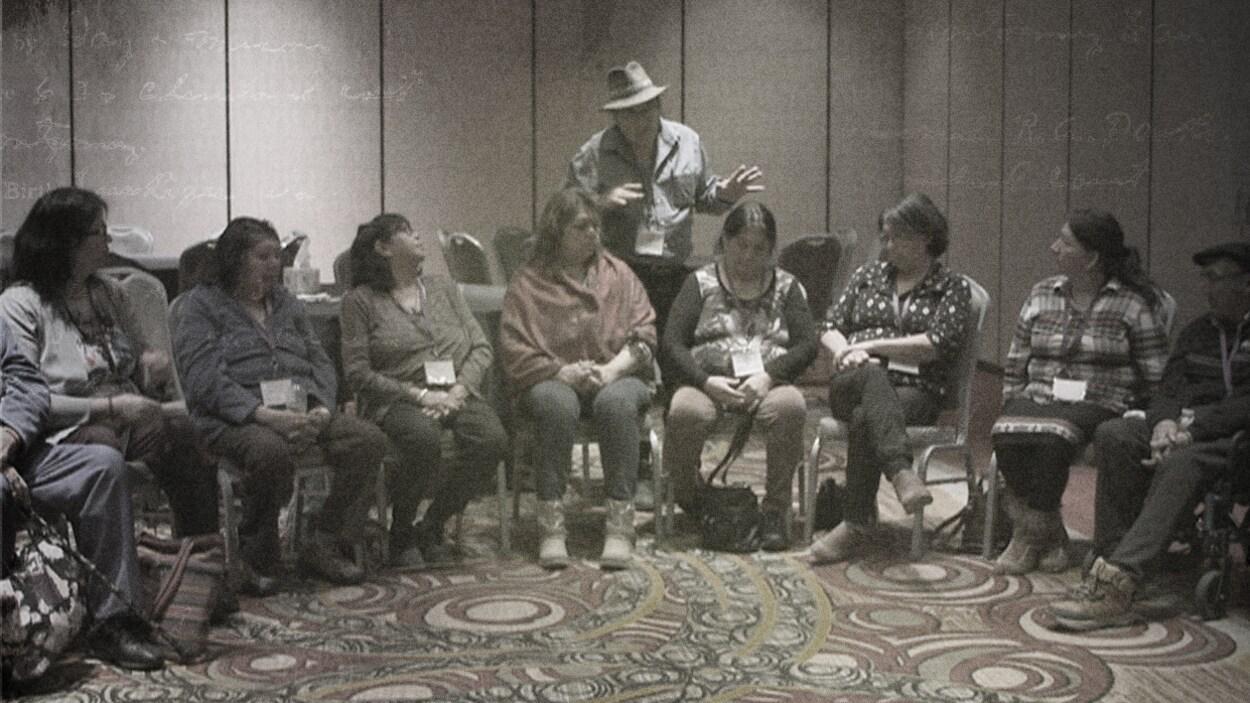 Une réunion de familles autochtones, assis en cercle sur des chaises.