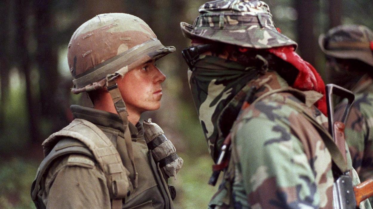 Un soldat de l'Armée canadienne et un Warrior se font face.