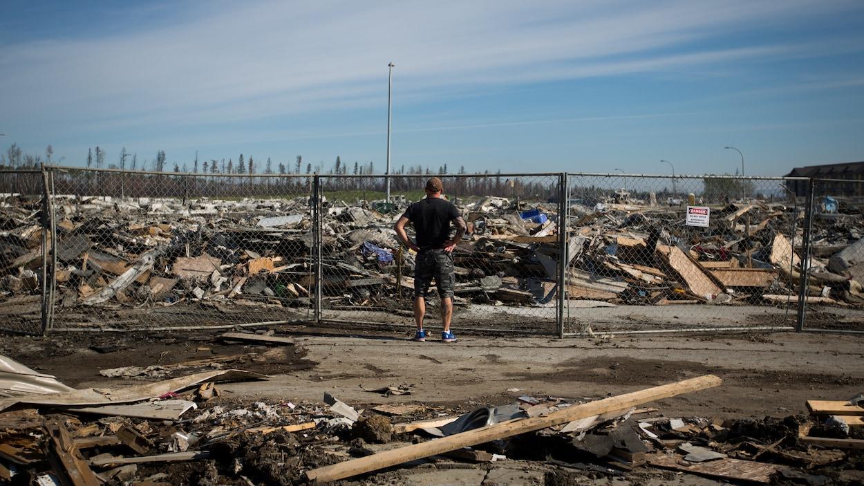 Un résident de Fort McMurray observe les ruines de sa résidence qui a été incendiée.
