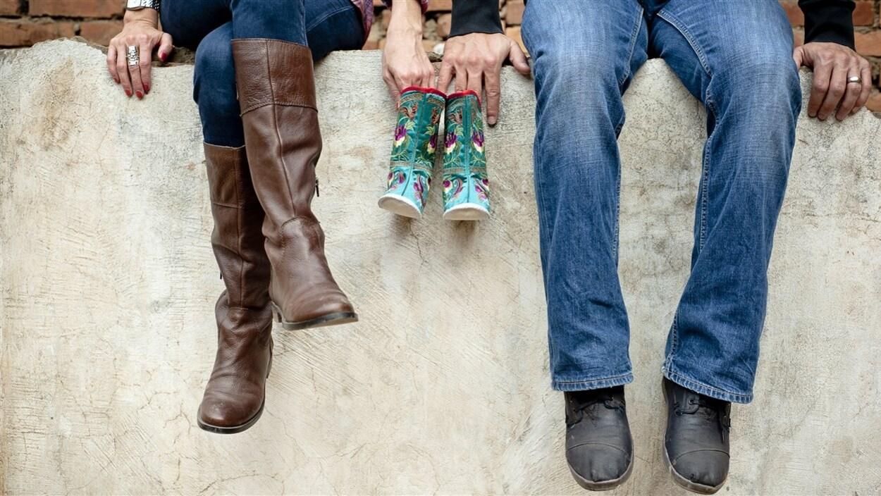 Un homme et une femme assis sur un mur de pierre, qui tiennent des bottes d'enfant.