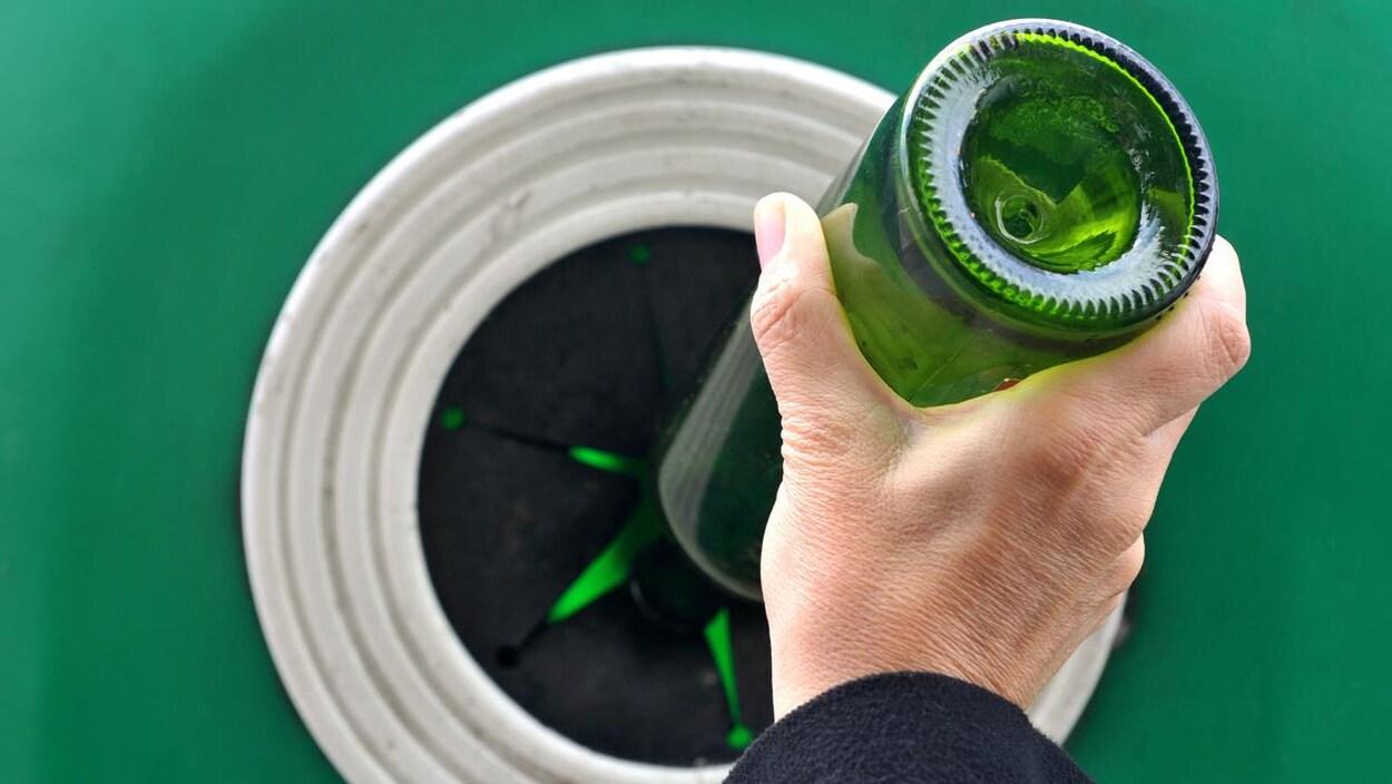 Photo d'une personne mettant une bouteille en verre dans un container de recyclage.