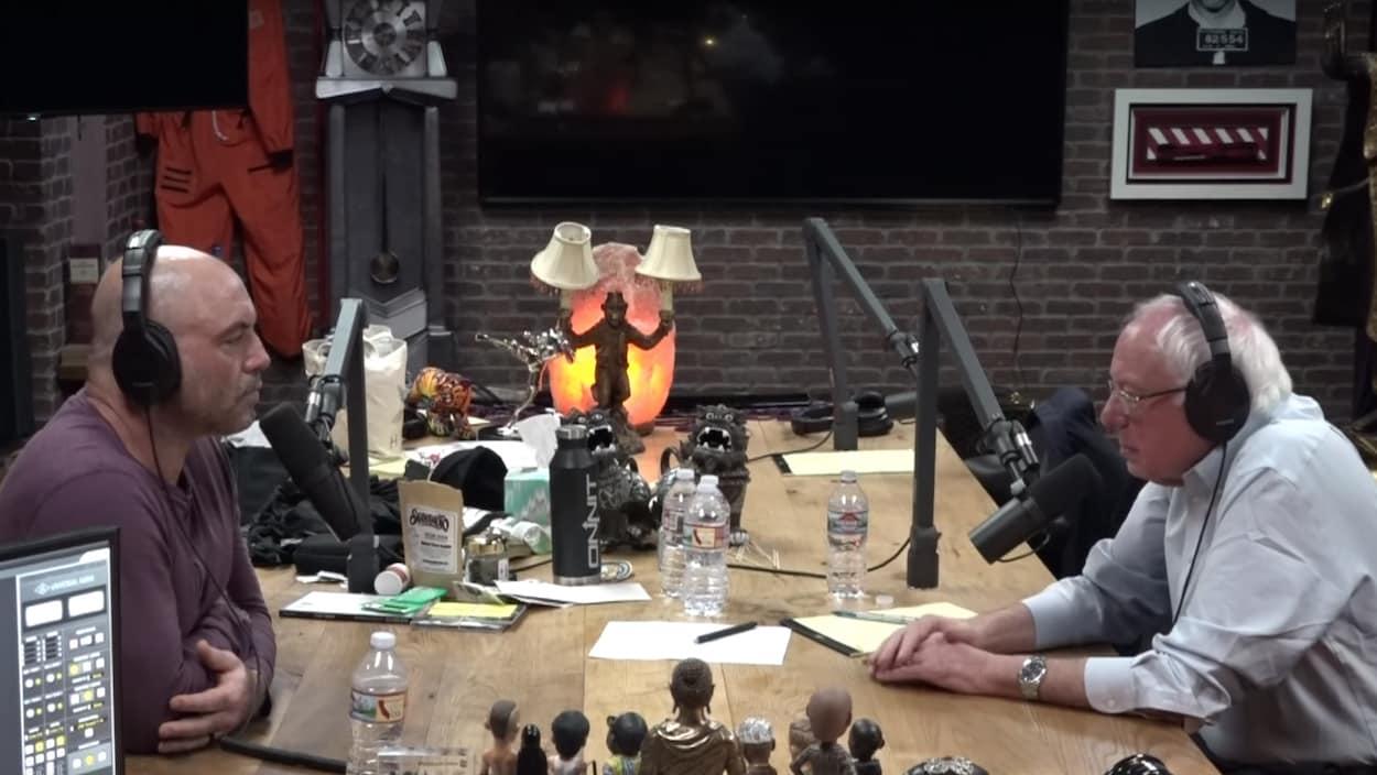 Deux hommes discutent autour d'une table dans un studio d'enregistrement.