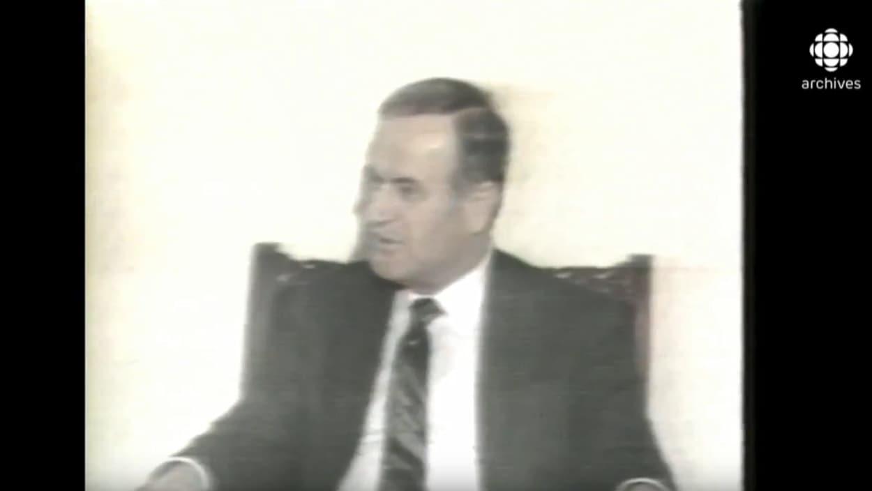 On voit un gros plan du président Hafez Al-Assad assis.