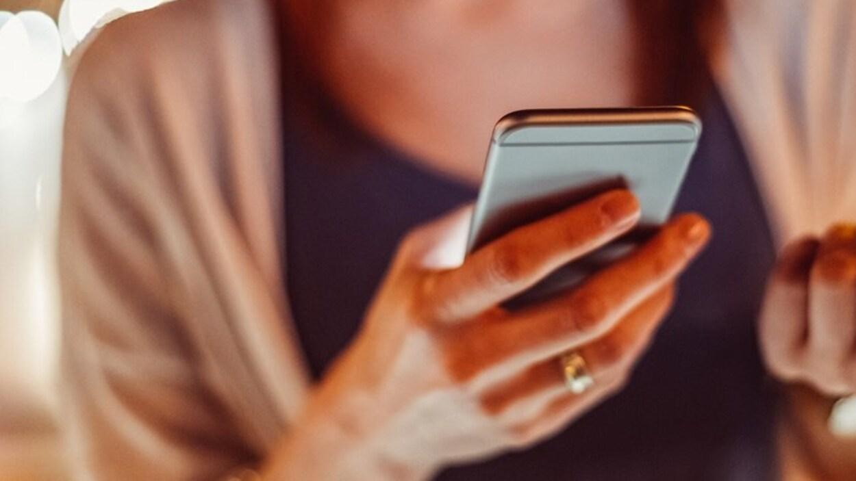 Une femme tient un cellulaire dans une main