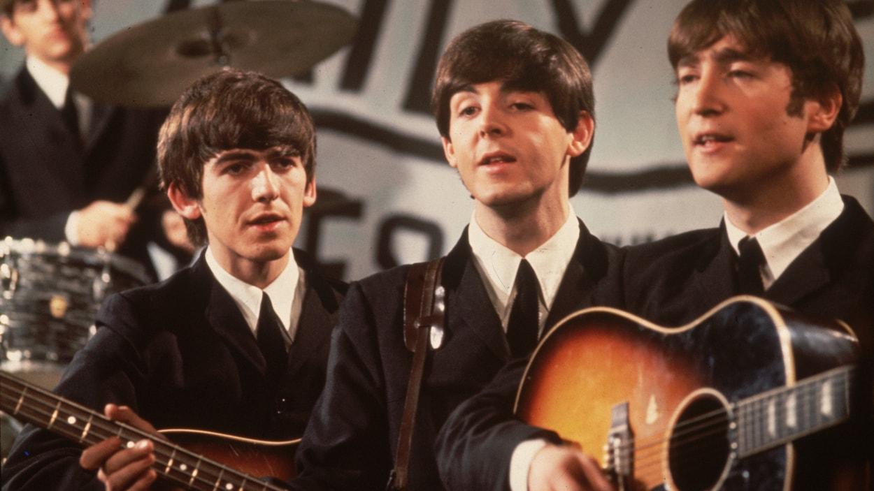 Une photo en couleurs des années 1960 montre les Beatles en complet noir pendant une performance.