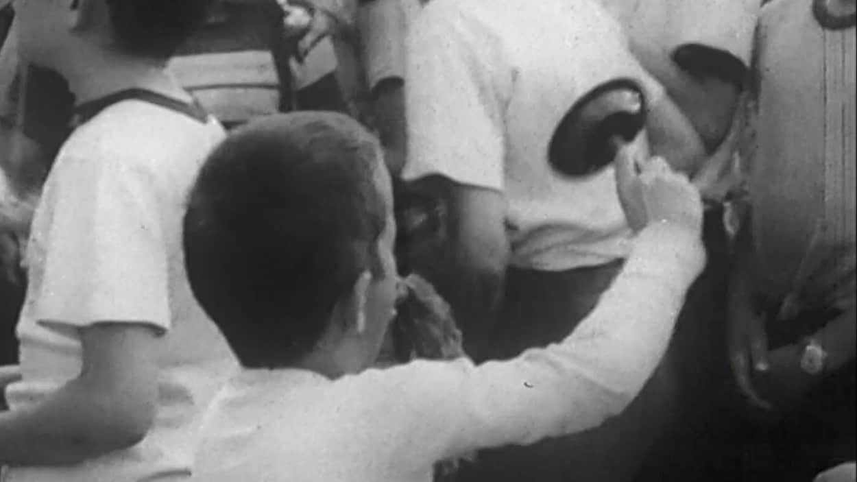Un garçon fait tourner une crécelle lors du tintamarre du 10 août 1955 à Moncton.