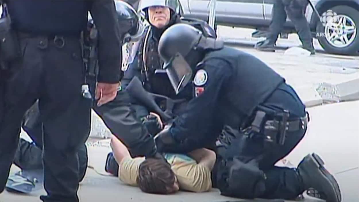 Un manifestant à bicyclette tombe par terre devant des policiers tenant des matraques et des boucliers de protection.