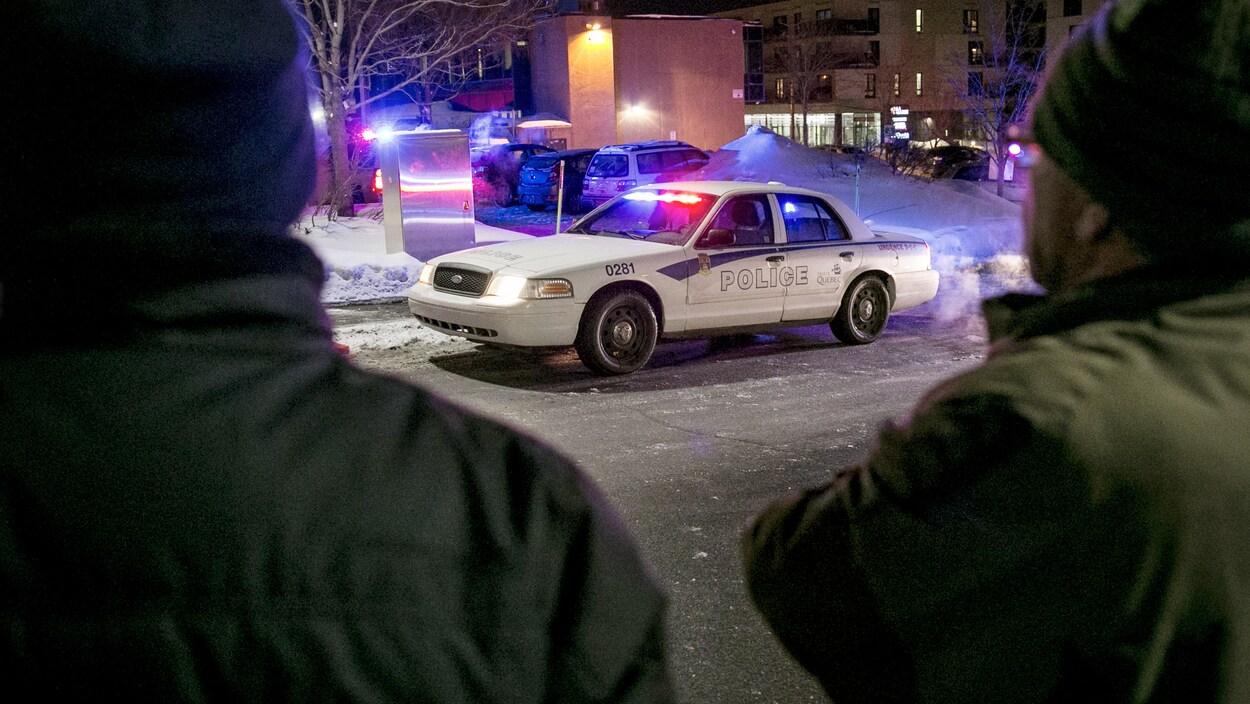 Deux hommes regardent la grande mosquée de Québec dans les instants après l'attentat.(archives)