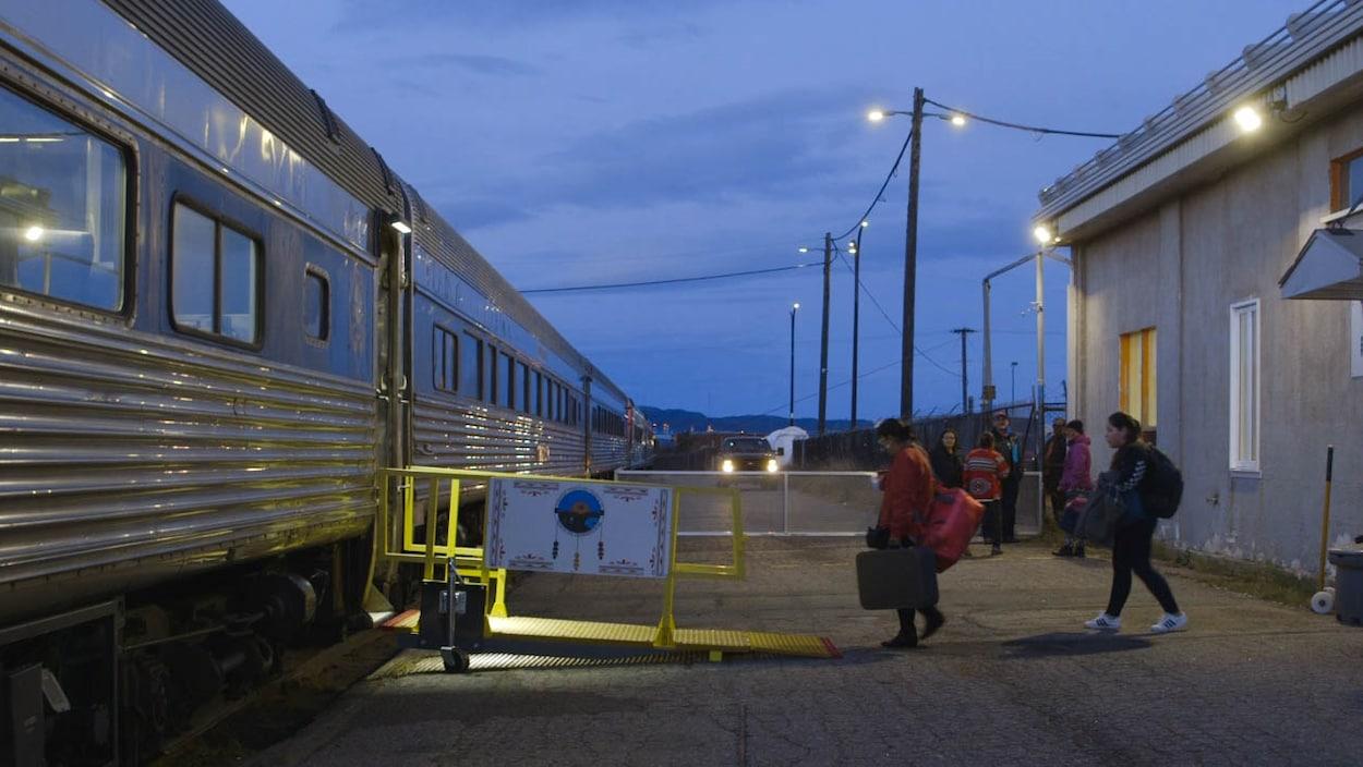 Des passagers sont sur le quai de la gare et s'apprêtent à monter dans le train.