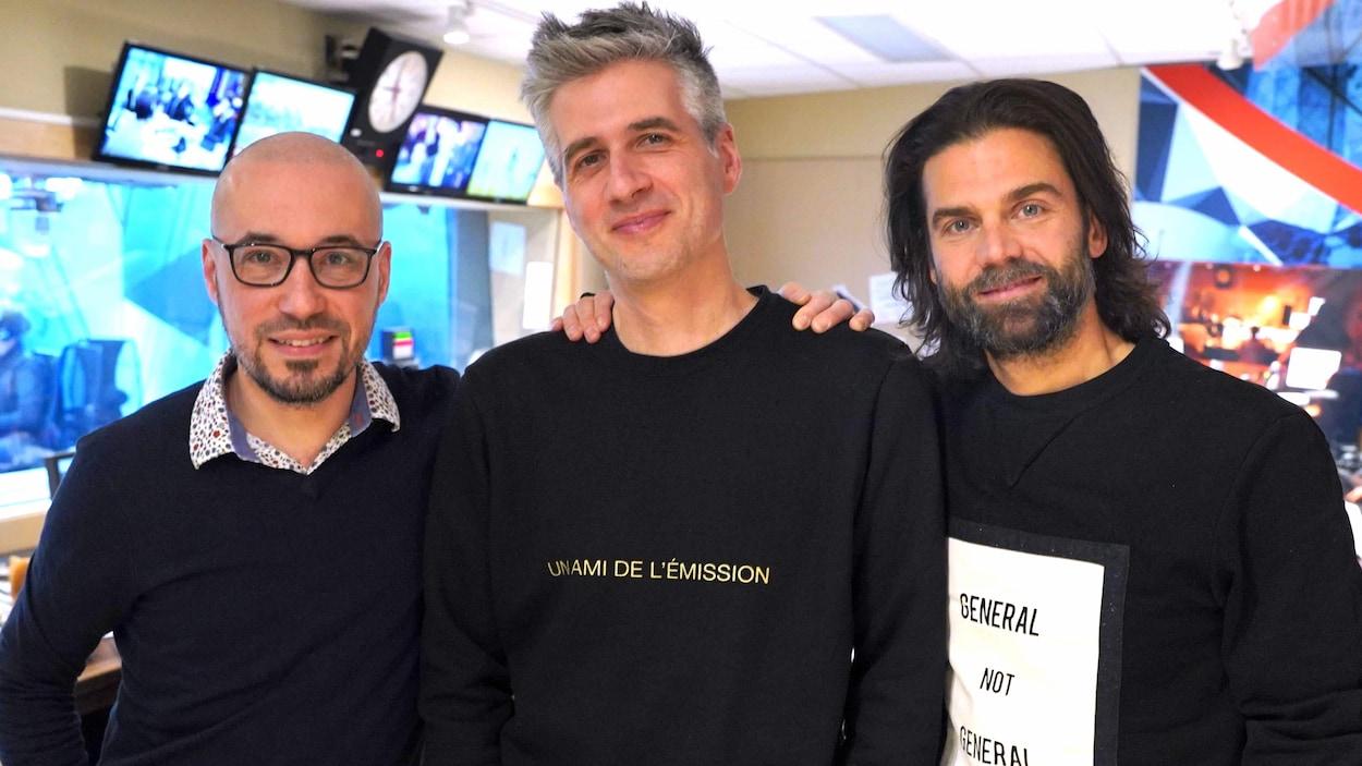 Les trois hommes sont debout, côté à côte.