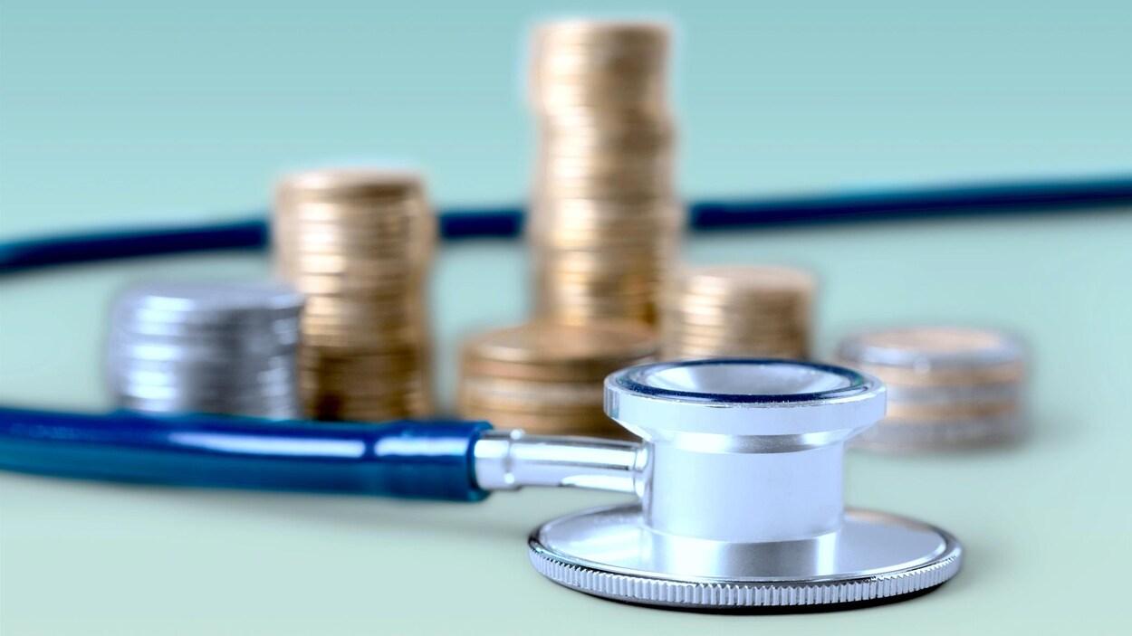 Un stéthoscope devant une pile de monnaie.