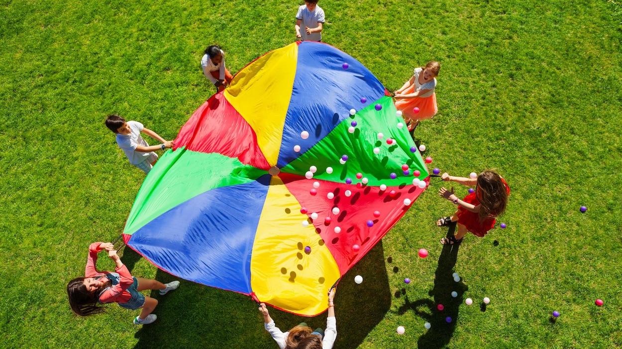Des enfants jouent au parachute.