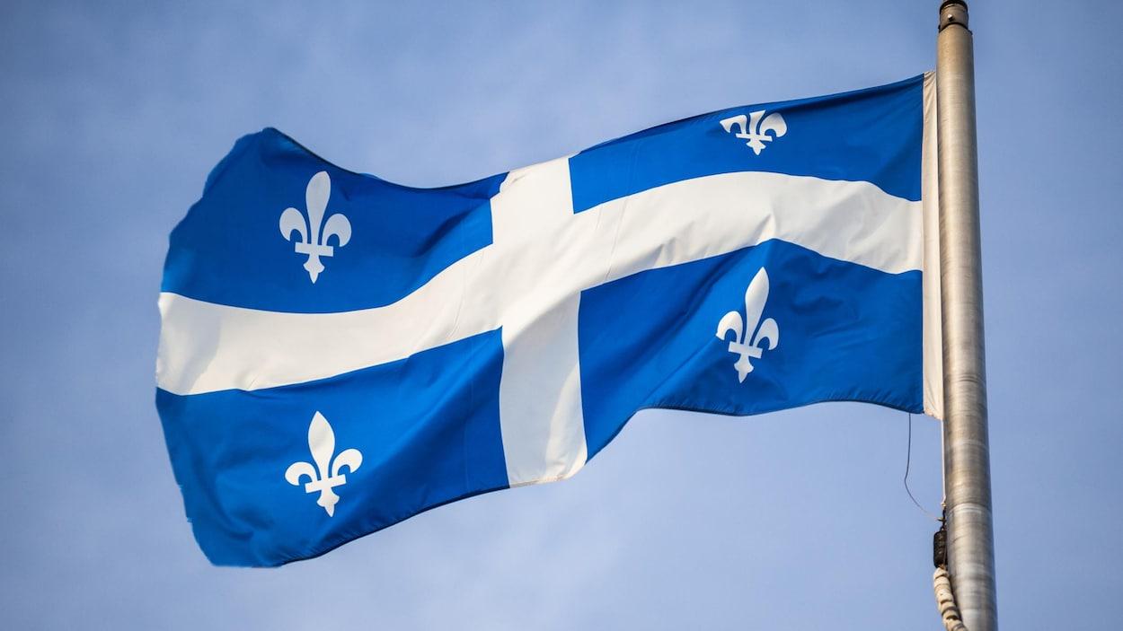 Le drapeau fleurdelisé, sur un mât, flotte au vent.