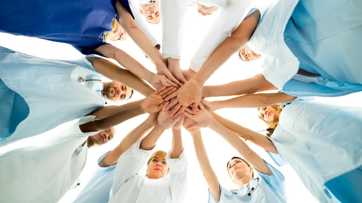 Des infirmières qui joignent leurs mains.