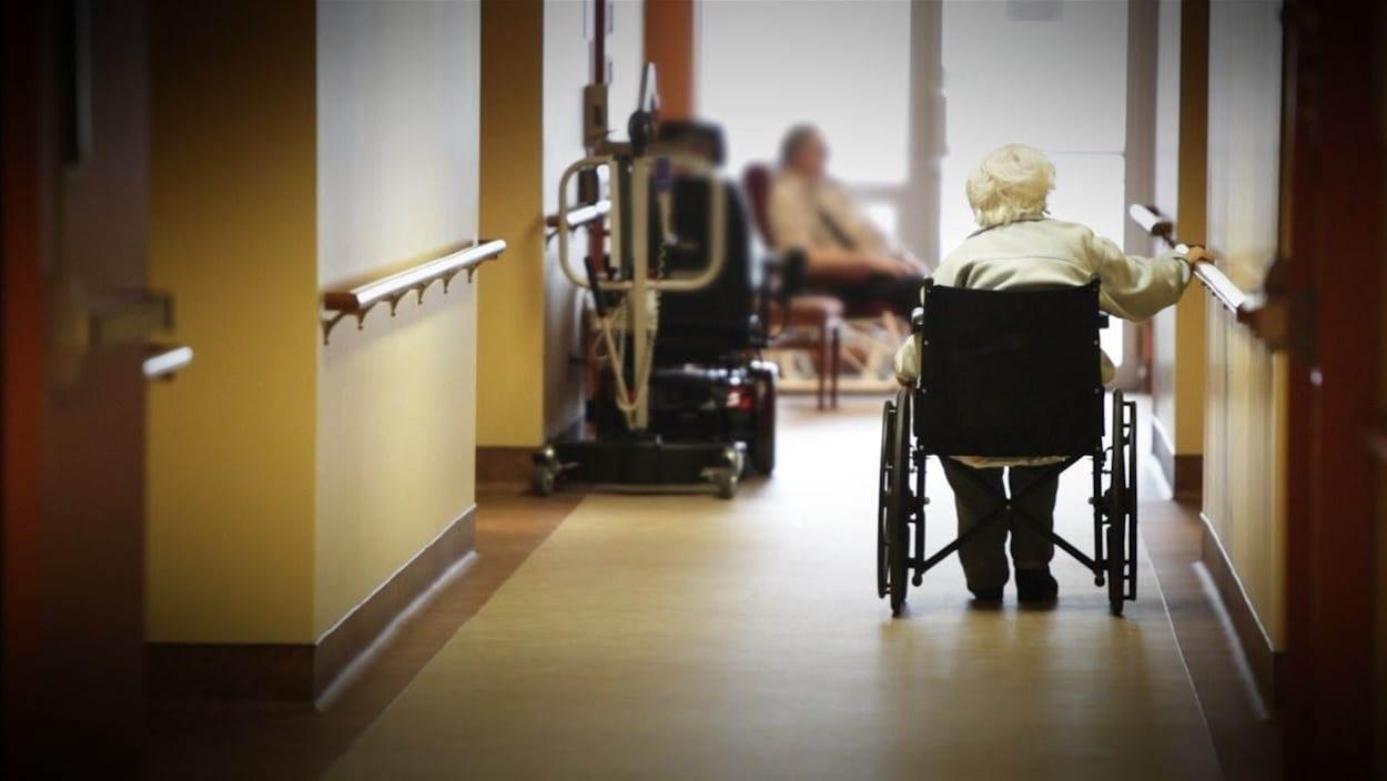 Une dame dans un fauteuil roulant dans le couloir d'un CHSLD.