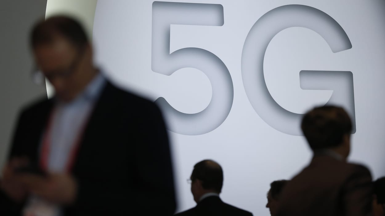 Des gens marchent devant une réclame publicitaire de la 5G au Mobile World Congress, à Barcelone, en février 2018.