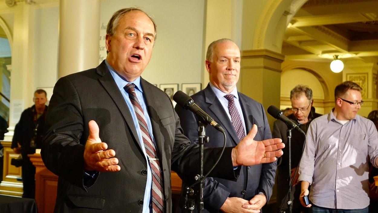 Le chef du Parti vert, Andrew Weaver, et le chef du Nouveau Parti démocratique (NPD), John Horgan, lors d'une conférence de presse à Victoria le mardi 30 mai