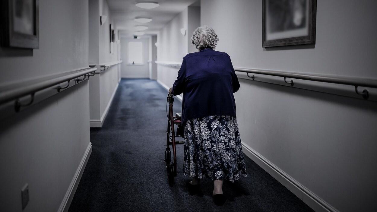 Une femme circule dans un couloir avec un déambulateur.