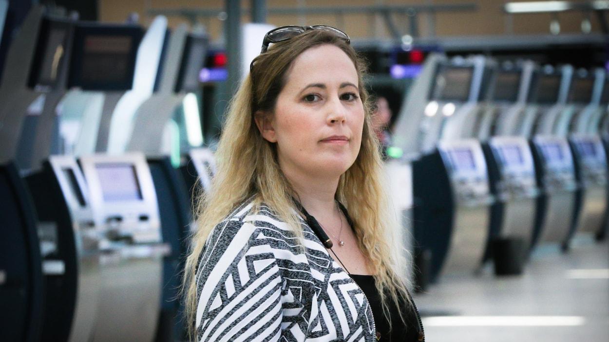 Jill Knapp se tient debout devant des bornes d'enregistrement à l'aéroport de Vancouver.