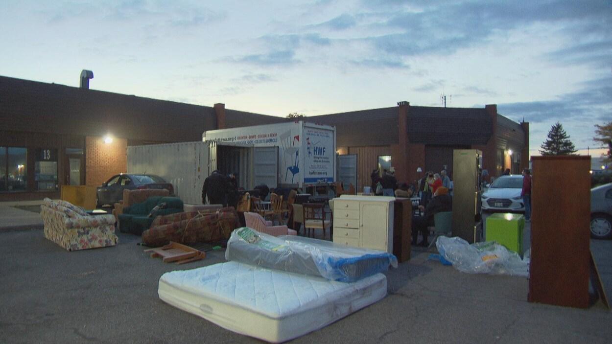 Tous les mercredis soirs, des bénévoles de l'organisme Aidons avec des meubles étalent les meubles et accessoires à donner dans un stationnement.