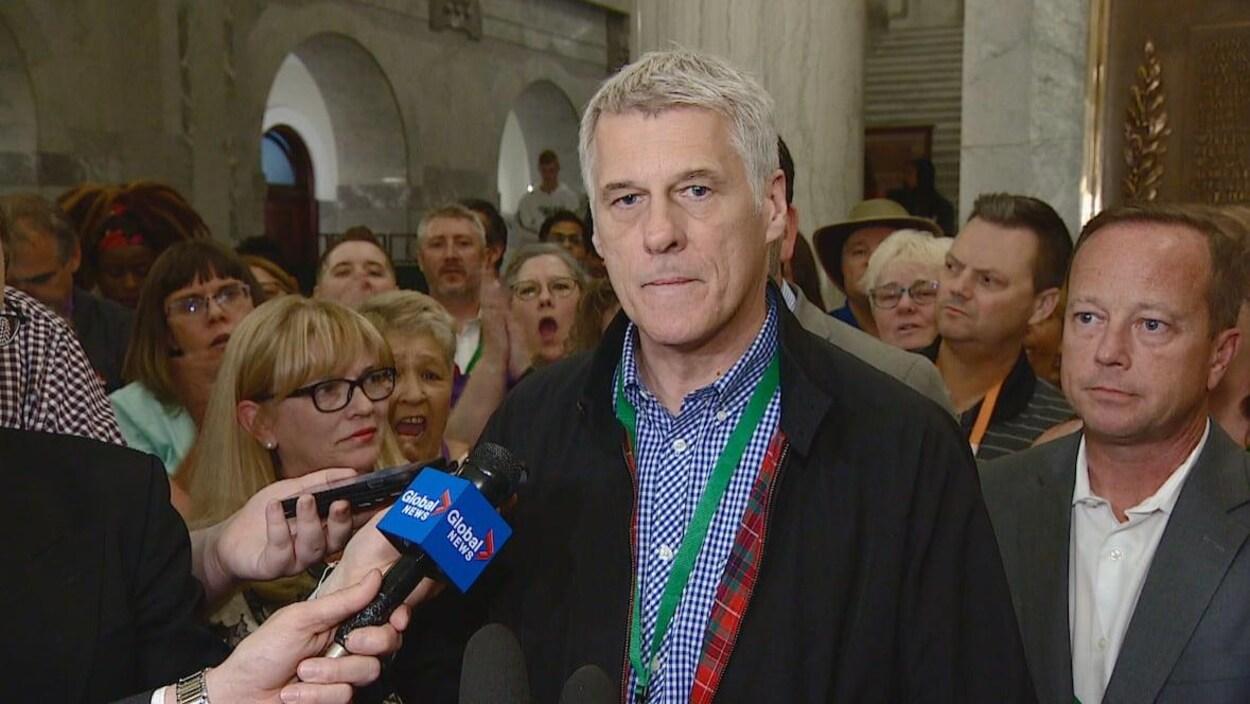 Un homme entouré de nombreuses personnes répond aux questions des journalistes au sein de l'Assemblée législative.