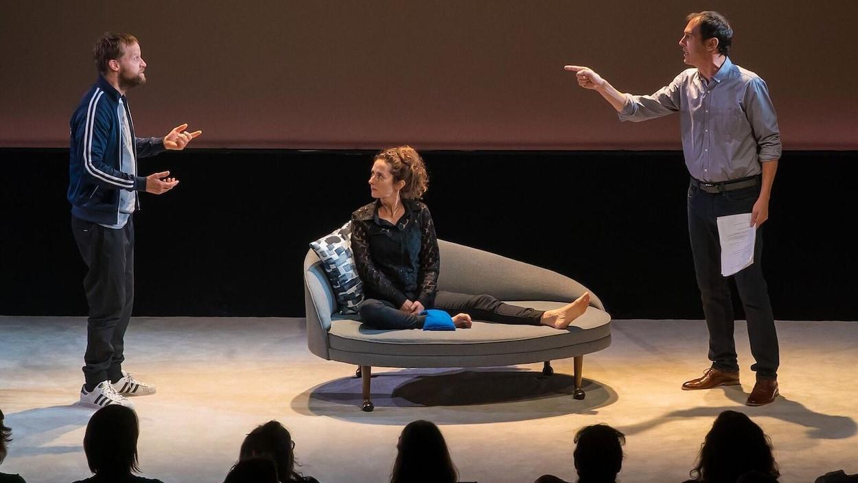 Une femme est assise sur un fauteuil sur une scène entre deux hommes qui argumentent.