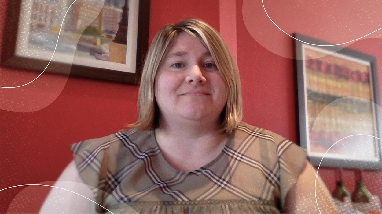 Une femme souriante assise devant la caméra.