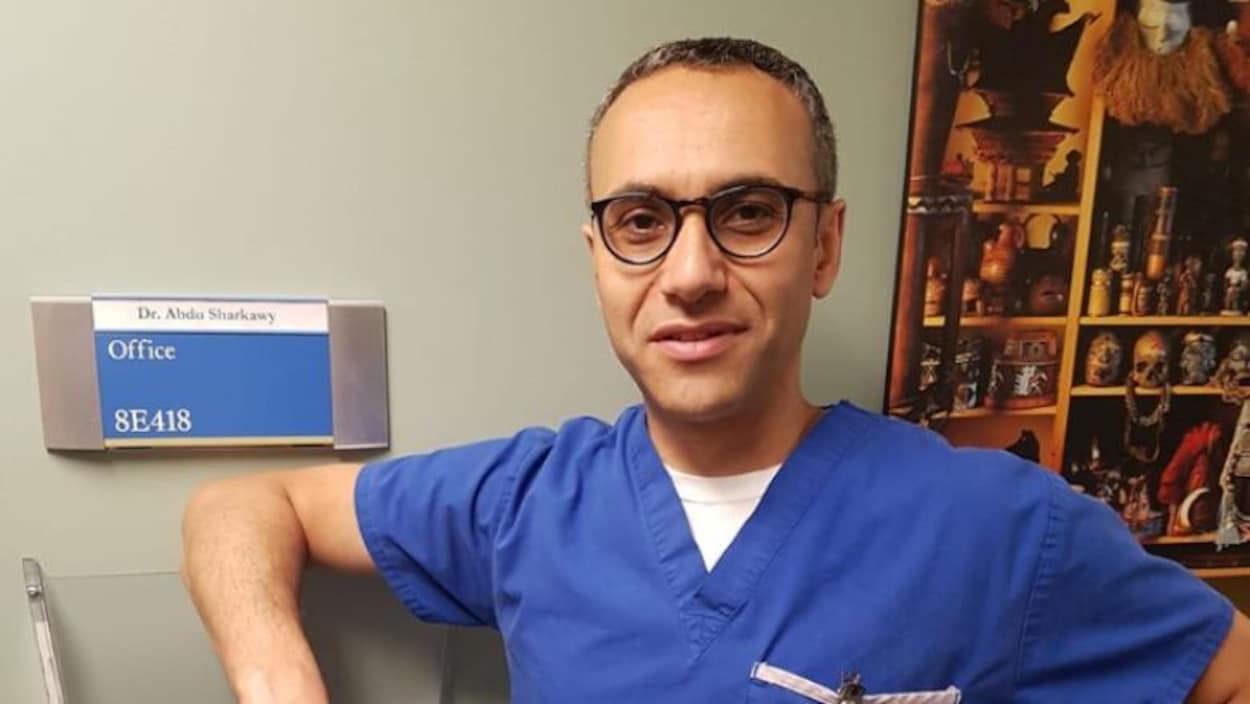 Le docteur Abdu Sharkawy, médecin spécialiste des maladies infectieuses, pose devant la porte de son bureau.