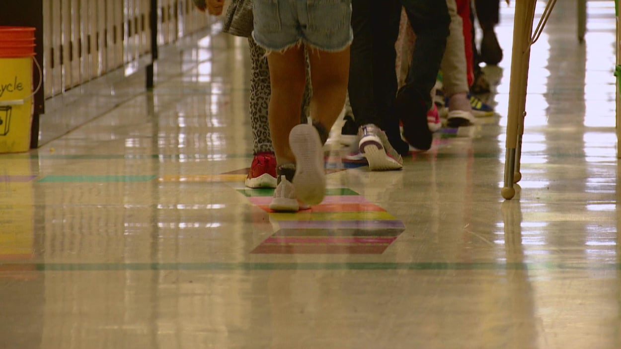Des élèves du primaire se déplacent dans un corridor d'école.