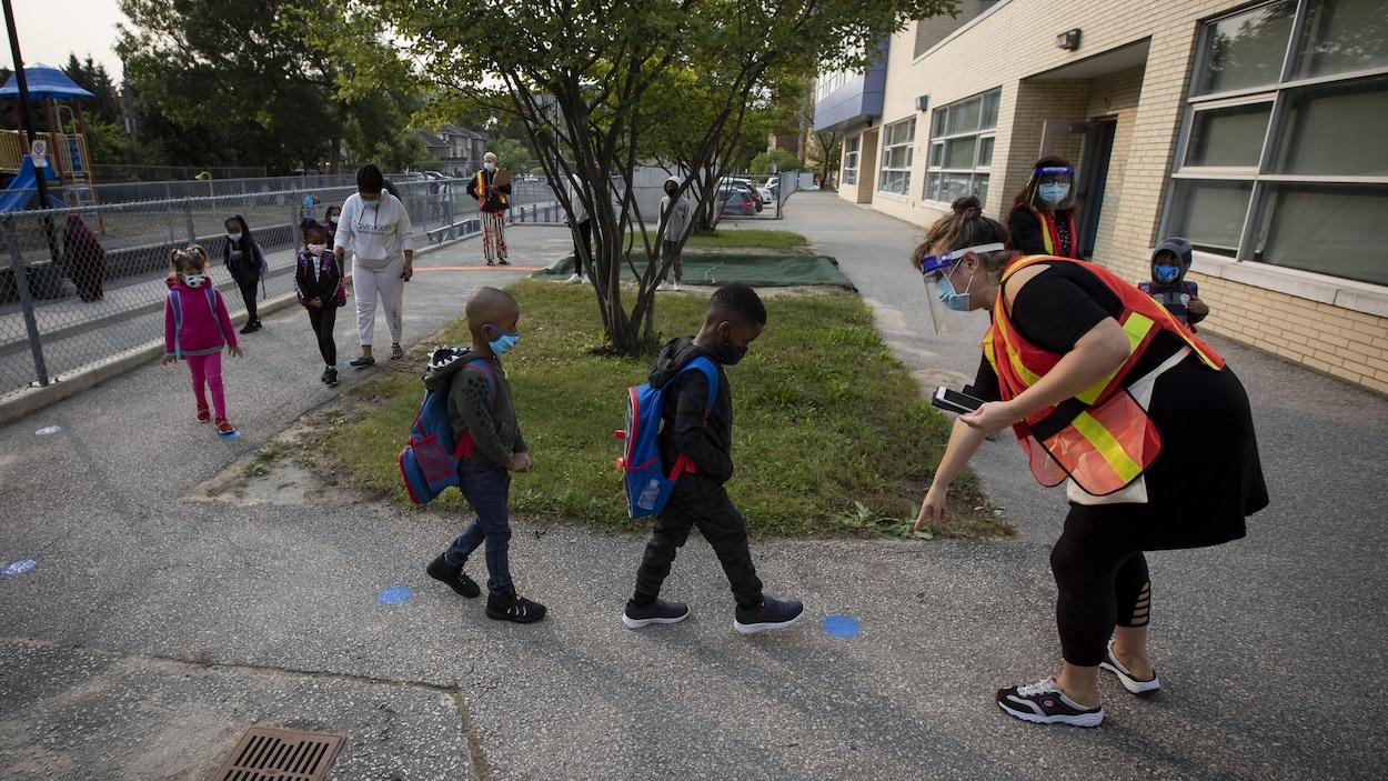 Des enfants marchent à la file dans l'enceinte d'une école de Toronto.