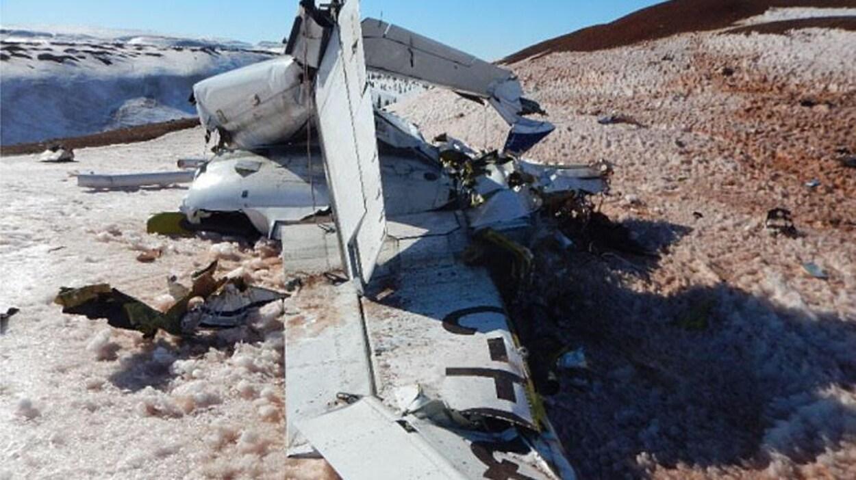 Épave de l'avion détruit dans un secteur un peu enneigé.