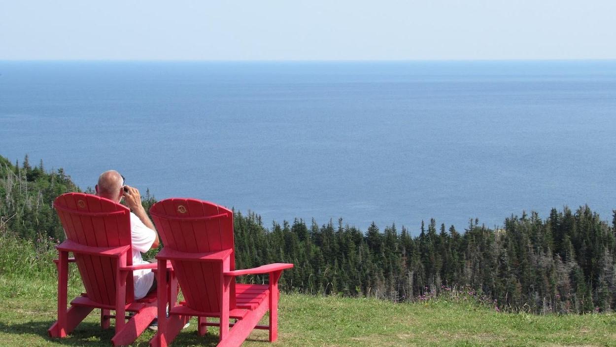 Un touriste observe la mer du haut de Cap-Gaspé assis sur une chaise rouge.