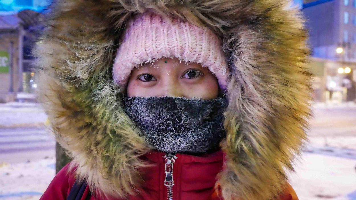 Une femme se couvre le visage pour lutter contre le froid.