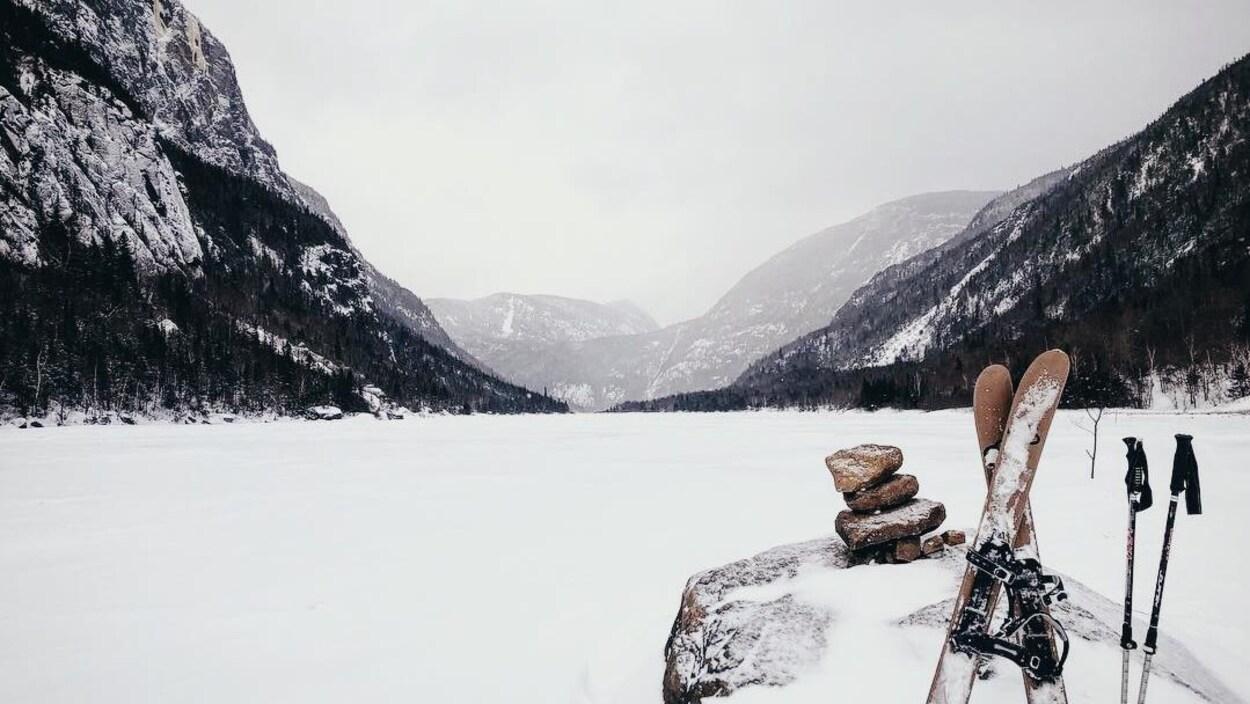 Une paire de skis-raquettes est appuyée contre une roche sur laquelle se trouve un Inuksuk. Derrière la rivière gelée continue à perte de vue vers le creux des montagnes.