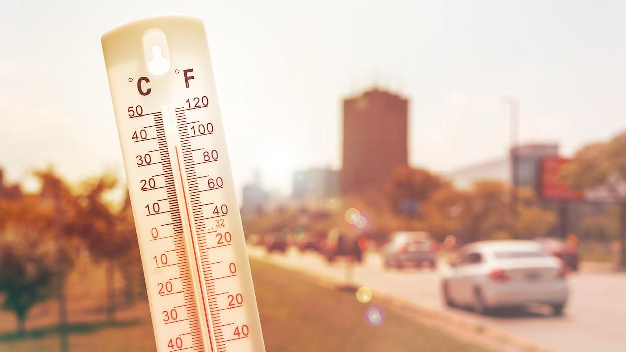 Un thermomètre devant un paysage urbain très ensoleillé.