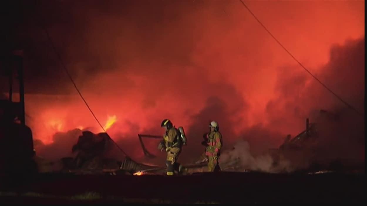Deux pompiers marchent devant des flammes et beaucoup de fumée.