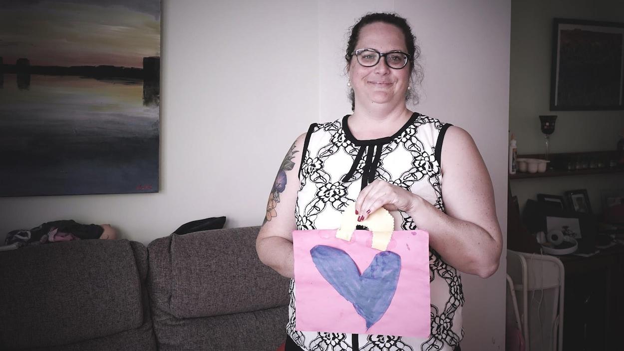 Isabelle N. Miron est debout dans son salon et tient ledit sac.