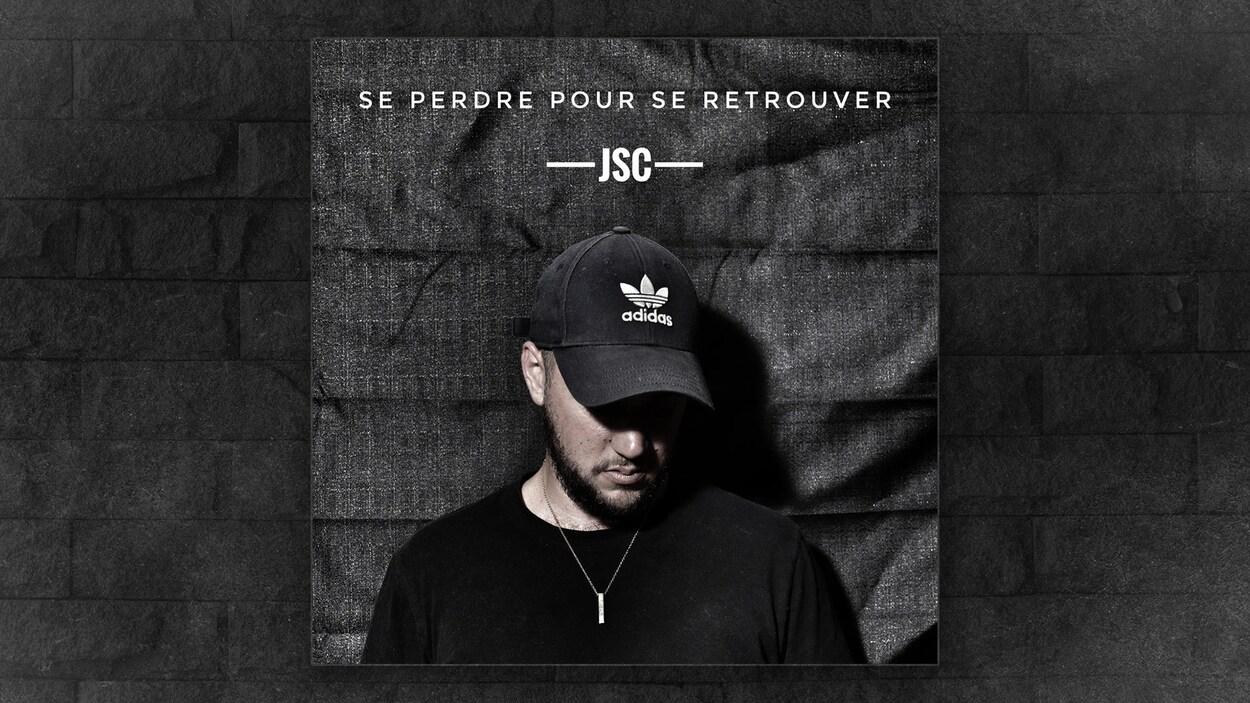 Une pochette d'album de musique illustrant un homme avec une casquette qui regarde vers le bas.