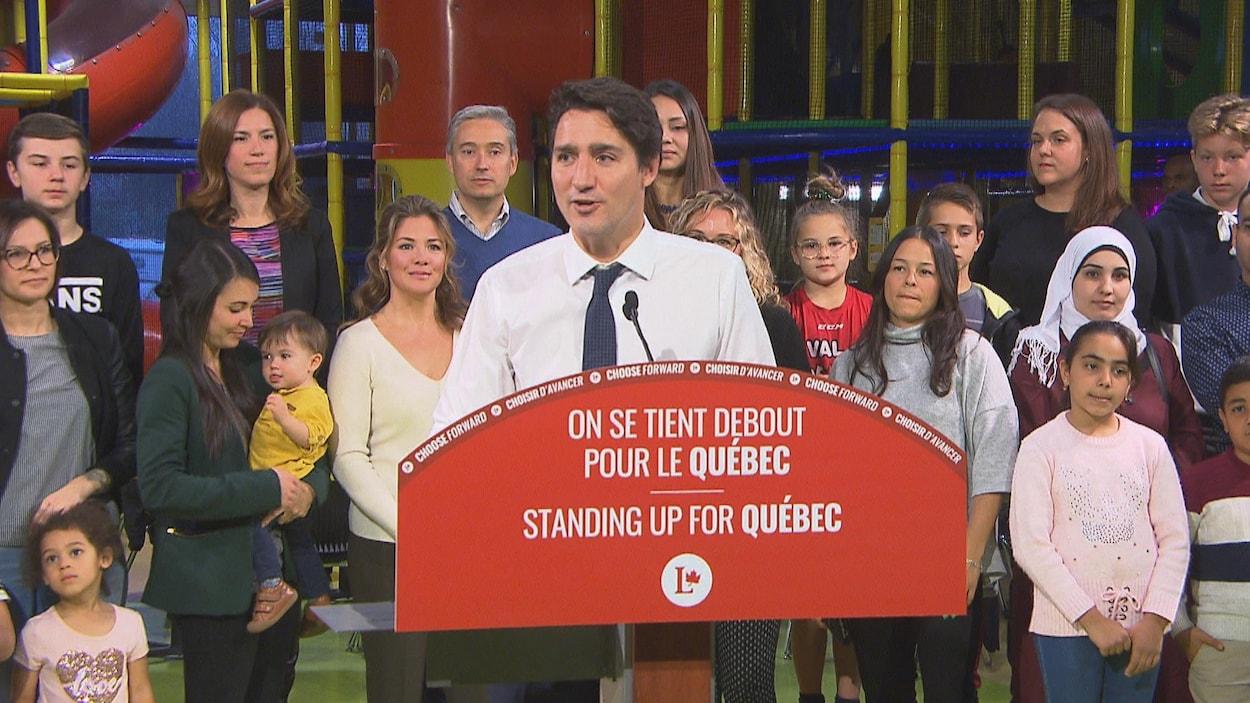 Le chef libéral Justin Trudeau au lutrin devant un groupe de femmes et d'enfants.