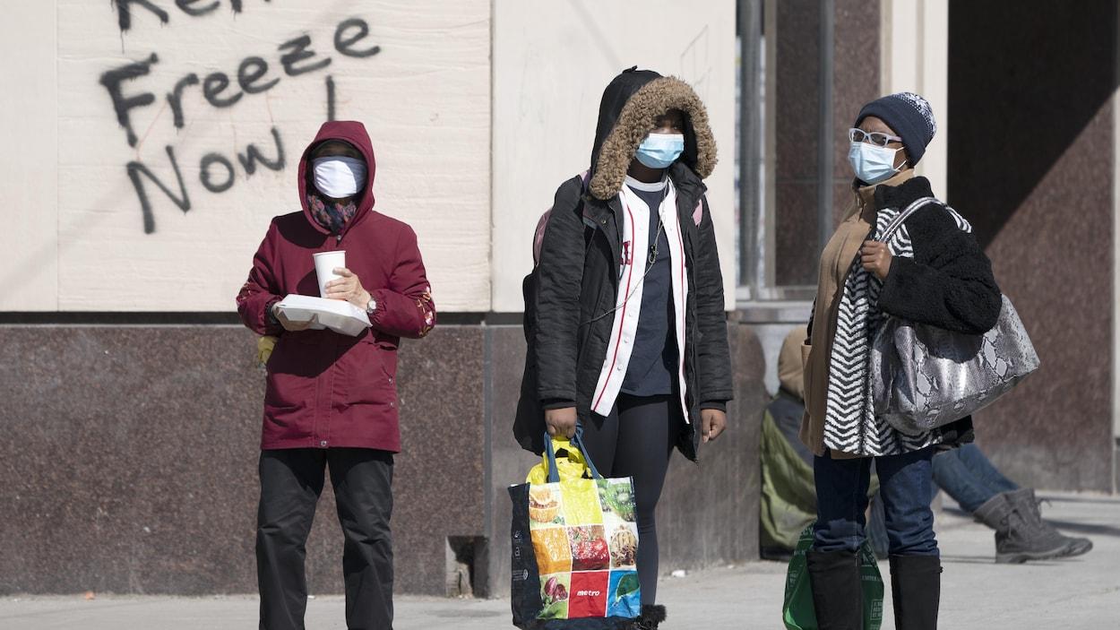 Des piétons masqués patientent sur un trottoir devant un graffiti demandant un gel des loyers.