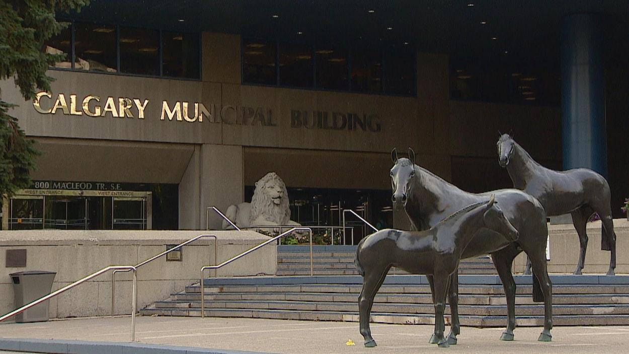 Entrée de l'hôtel de ville de Calgary. Des statues de troix chevaux sont placées sur des marches. Une statue de lion est placée devant les portes d'entrée.